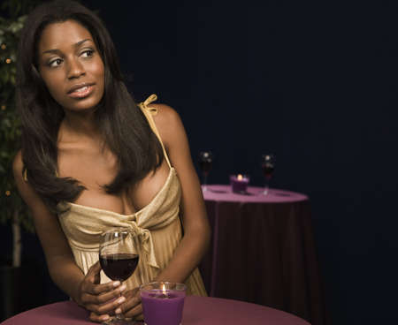 stood up: African woman holding glass of wine