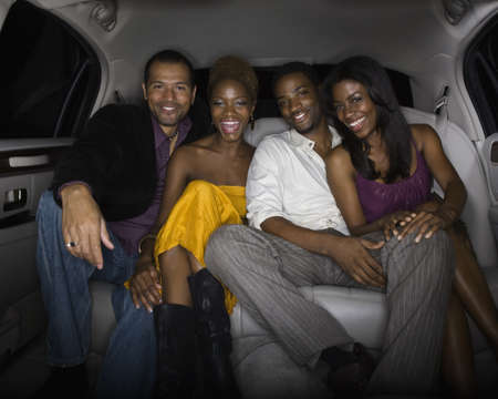 Multi-ethnic friends in back of limousine