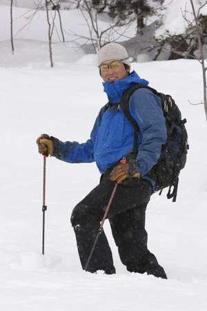 cros: Asian man walking in snow
