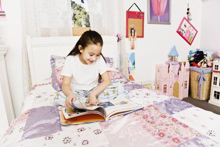 devilment: Asian girl reading on bed LANG_EVOIMAGES