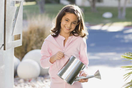 snoozing: Hispanic girl holding watering can