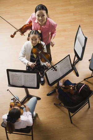 performing: Asian female music teacher helping student play violin