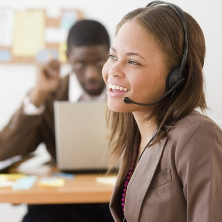 customer service representative: African businesswoman wearing headset LANG_EVOIMAGES