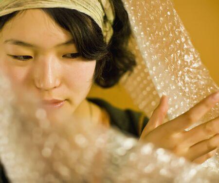 unwrapping: Asian woman pushing aside bubble pack