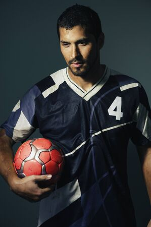 pacific islander ethnicity: Hispanic male soccer player holding ball LANG_EVOIMAGES