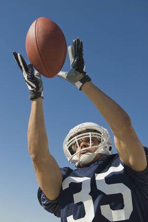 davenport: Hispanic male football player catching ball LANG_EVOIMAGES