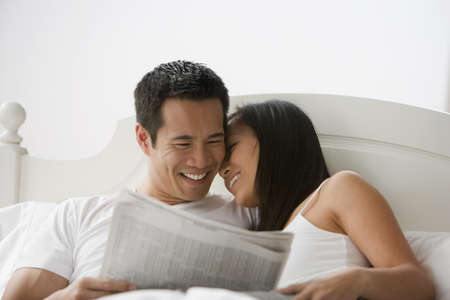telecommuter: Asian couple reading newspaper in bed