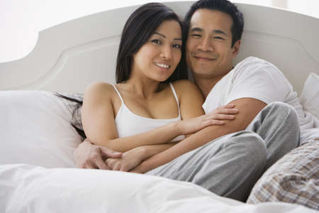 Asian couple hugging in bed