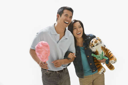 Asian couple holding cotton candy and stuffed animal