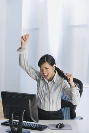 shrieking: Asian businesswoman cheering at desk