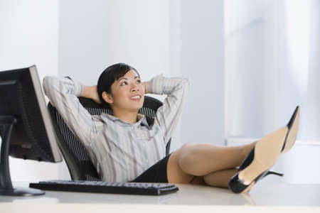 desk: Asian businesswoman with feet on desk