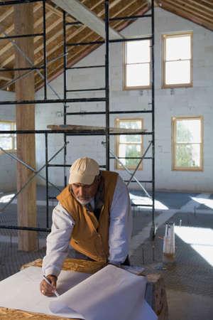 architect: Hispanic architect drawing on blueprints