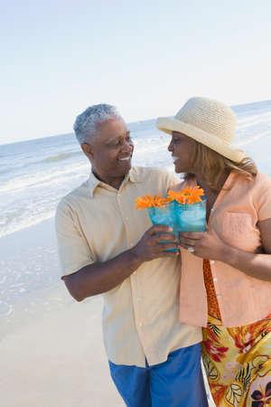 babyboomer: African couple walking on beach