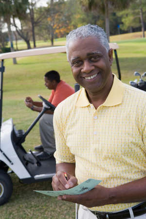 fathering: African father and adult son on golf course LANG_EVOIMAGES