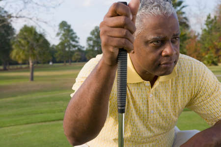 seriousness skill: African man holding golf club