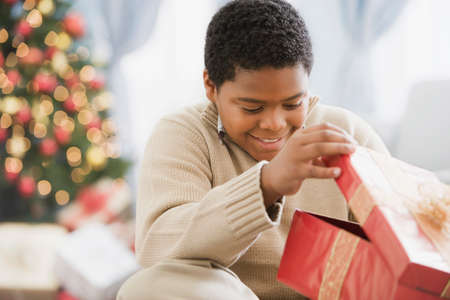 zeal: African boy opening gift LANG_EVOIMAGES