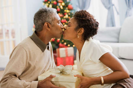 African couple kissing on Christmas