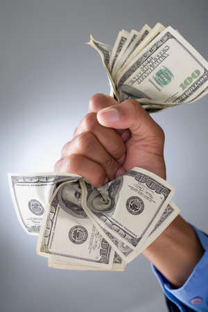 clenching fists: Mixed Race businessman holding money