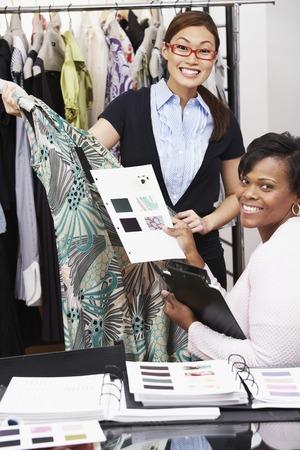 Multi-ethnische Mode-Designer halten Entwürfe und Kleid