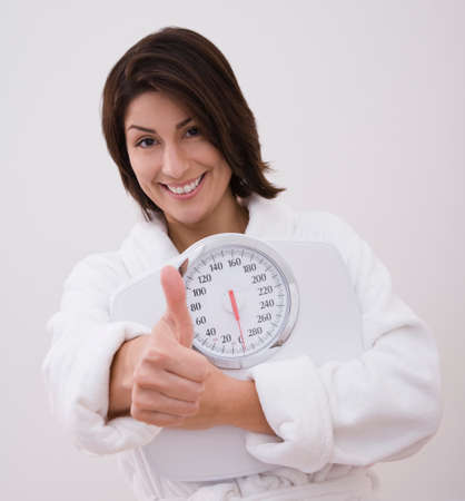 motioning: Hispanic woman holding scale and giving thumbs up