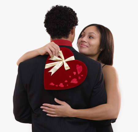 bestowing: African woman holding valentine's gift and hugging boyfriend LANG_EVOIMAGES