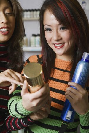 hair product: Multi-ethnic female hair stylists looking at hair product