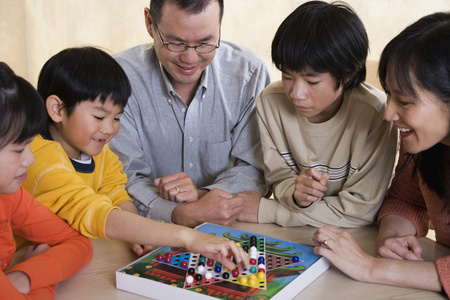 Asian family playing board game Imagens