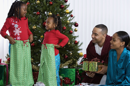 new age: African sisters holding matching Christmas gifts LANG_EVOIMAGES