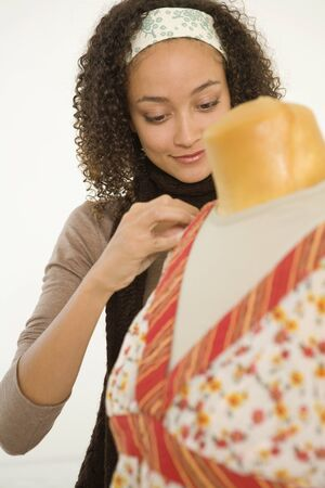 pinning: African woman pinning fabric on dress dummy