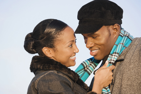 tugging: Multi-ethnic couple smiling at each other