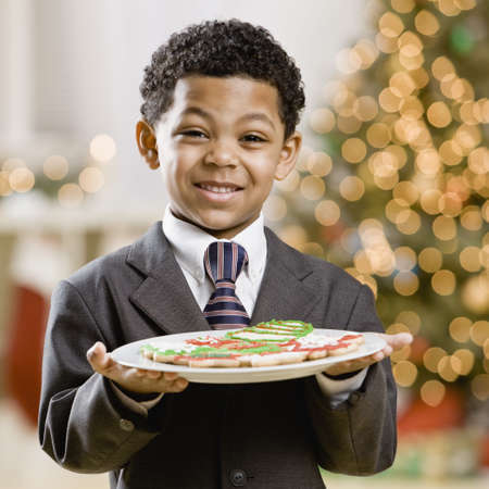exactitude: Mixed Race boy holding plate of Christmas cookies LANG_EVOIMAGES