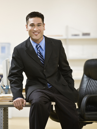 Asian businessman sitting on edge of desk 스톡 콘텐츠