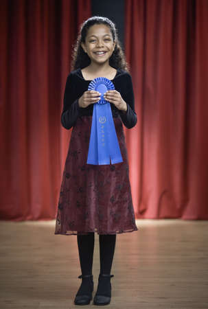 reciting: Mixed Race girl holding blue ribbon on stage