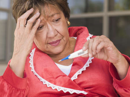 low spirited: Senior Hispanic woman looking at thermometer