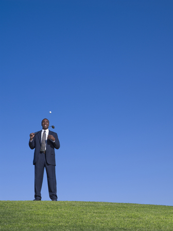 African businessman playing golf