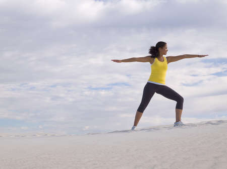 colo: Mixed Race woman practicing yoga on sand dune