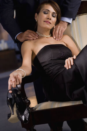 massaged: Hispanic woman in evening gown having shoulders massaged LANG_EVOIMAGES