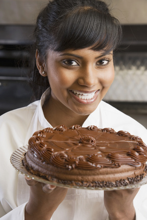 Mixed Race female pastry chef holding cake
