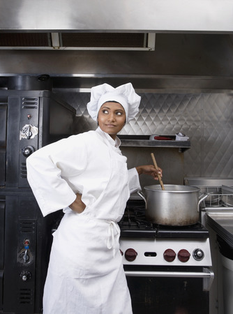 Mixed Race female chef preparing food Stock Photo