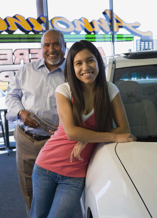 commercialism: Hispanic father and daughter in car dealership