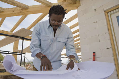 acknowledging: African architect looking at blueprints on construction site