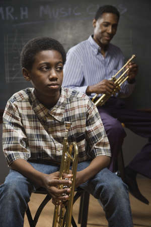 teacher and student: African man and boy holding trumpets in classroom