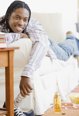African man watching television on sofa