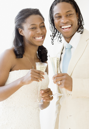 African bride and groom holding champagne flutes 免版税图像