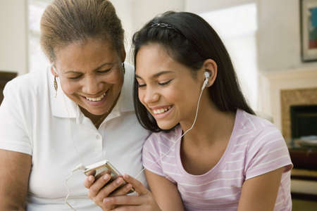gramma: Hispanic grandmother and granddaughter listening to music on mp3 player LANG_EVOIMAGES