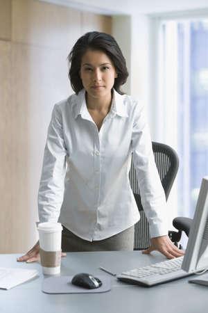unyielding: Eurasian businesswoman looking stern in office