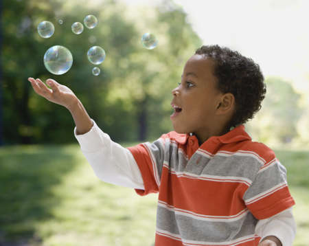 African boy catching bubbles Stock Photo