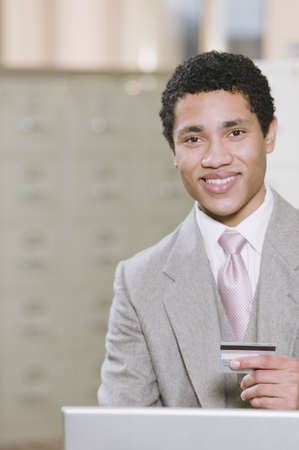 commercialism: Mixed race businessman with laptop holding credit card