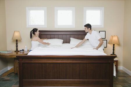 Hispanic couple making bed 스톡 콘텐츠