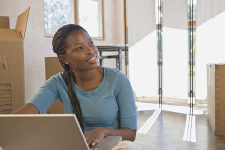 telecommuter: African woman next to laptop in new home